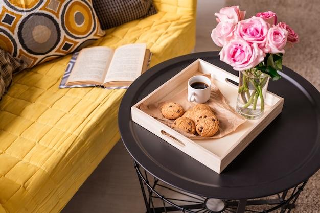 Huisstilleven met bos roze rozen, zelfgemaakte snack en drankje op tafeltje en open boek en kussens op gele bank