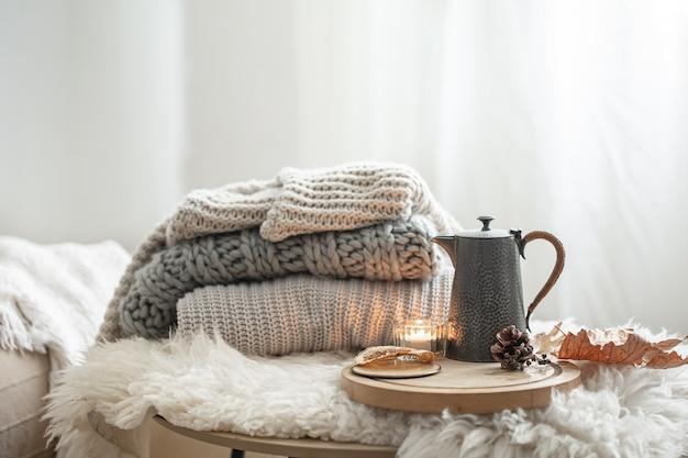 Huisstilleven met gebreide truien en theepot thee op wazige achtergrond kopie ruimte.