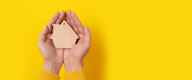 Huisstuk speelgoed in handen over gele achtergrond, panoramische mock-up