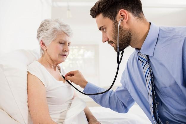 Huisverpleegster die aan borst van patiënt met stethoscoop thuis luisteren
