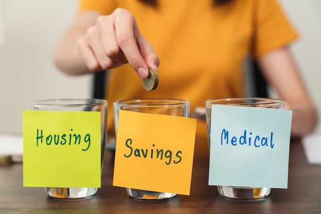Huisvesting, medisch met spaarpapier op de fles geplakt met munten erin, jonge vrouw gebruikt een rekenmachine en plant inkomsten en uitgaven gedeeld door categorieën.