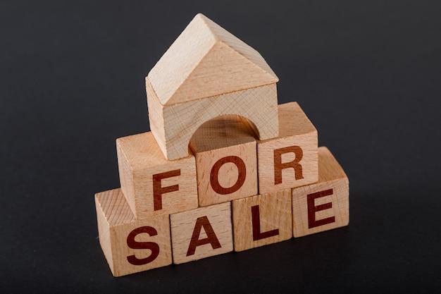 Huisvesting voor verkoopconcept met houten kubussen, houten stuk speelgoed huis op donkere hoogte.