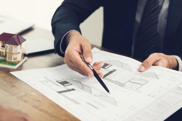Huisvestingsontwikkelaar of architect die blauwdrukpapier houden en ontwerpconcept verklaren