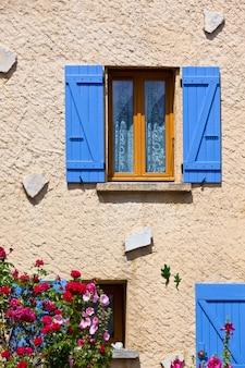 Huisvoorgevel met blauwe blinden in frankrijk. verticale opname