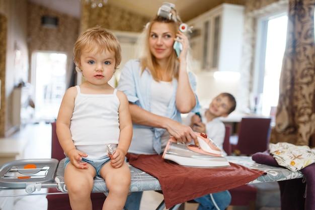 Huisvrouw aan het telefoneren, kinderen in de keuken aan het dollen. vrouw met kinderen die thuis samen spelen. vrouwelijke persoon met dochter en zoon in hun huis