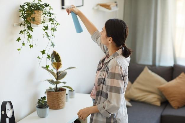 Huisvrouw bedrijf spray fles en binnenlandse bloemen aan de muur in de kamer thuis water geven
