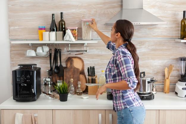 Huisvrouw bereidt ontbijt in de keuken
