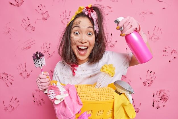 Huisvrouw blij dat ze klaar is met het schoonmaken van het huis houdt borstelspray vast met wasmiddel staat vies op roze