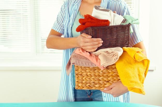 Huisvrouw brengt een enorme stapel wasgoed op de strijkplank