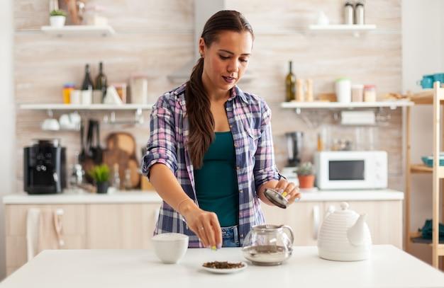 Huisvrouw die aromatische kruiden gebruikt om hete natuurlijke thee te maken om van het ontbijt te genieten