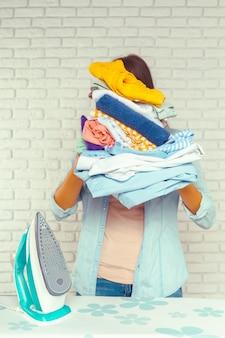 Huisvrouw die een enorme stapel wasgoed op de strijkplank brengt