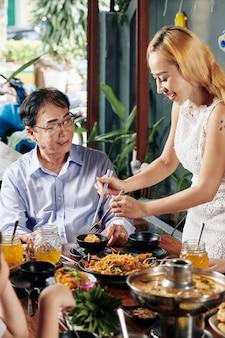 Huisvrouw die eten serveert voor schoonvader