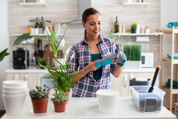Huisvrouw die handschoen draagt voor tuinieren terwijl ze voor bloemen zorgt in de keuken thuis