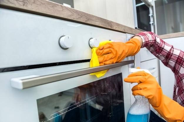 Huisvrouw die het gasfornuis met wasmiddel in de keuken wast. huis schoonmaken.