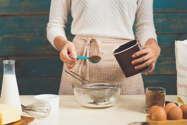 Huisvrouw die het maken van schorten draagt. stappen voor het maken van het koken van chocoladetaart.