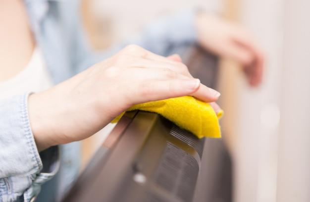 Huisvrouw die het stof van de tv in de woonkamer schoonmaakt