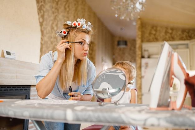 Huisvrouw die make-up aanbrengt op de strijkplank, kleine baby kijkt naar haar. vrouw met kind samen thuis