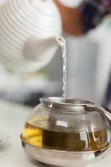 Huisvrouw die natuurlijke groene thee voorbereidt voor het ontbijt in de keuken