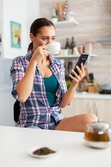 Huisvrouw die 's ochtends tijdens het ontbijt hete groene thee drinkt met smartphone
