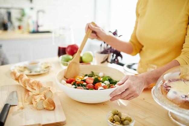 Huisvrouw die salade voor diner maakt