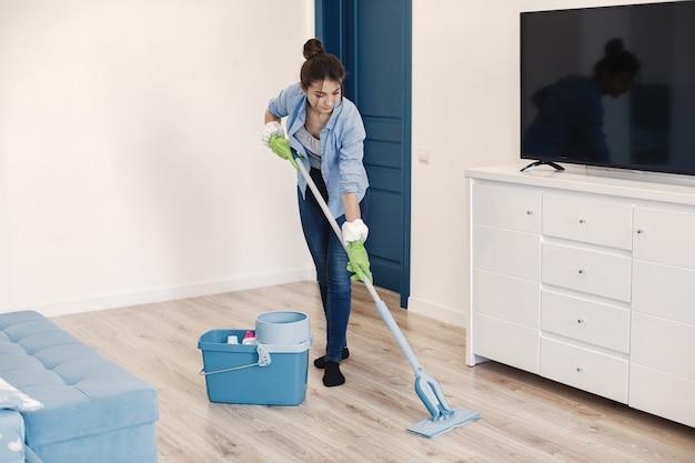 Huisvrouw die thuis wakker wordt. dame in een blauw shirt. vrouw schone vloer.