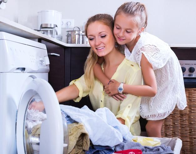 Huisvrouw en meisje die wasserij doen