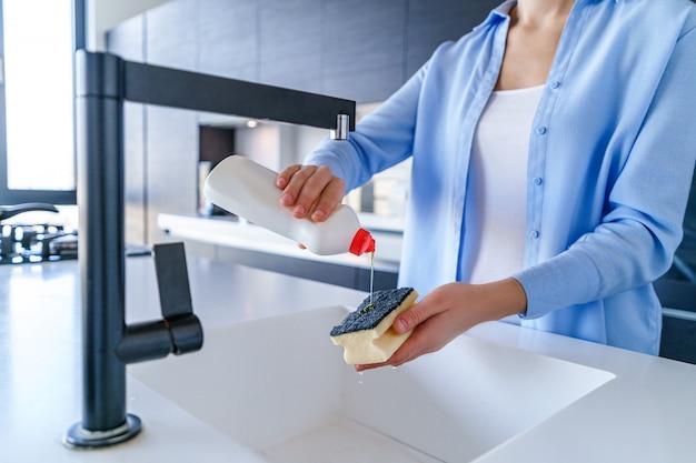 Huisvrouw gebruikt afwasmiddel voor het afwassen van gerechten in de keuken thuis