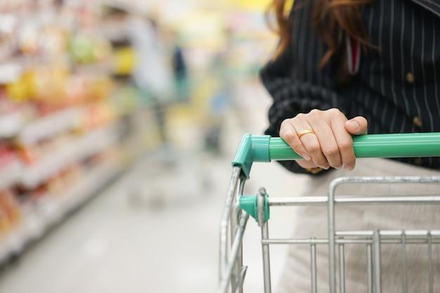 Huisvrouw hand touch trolley bar om te winkelen op de markt