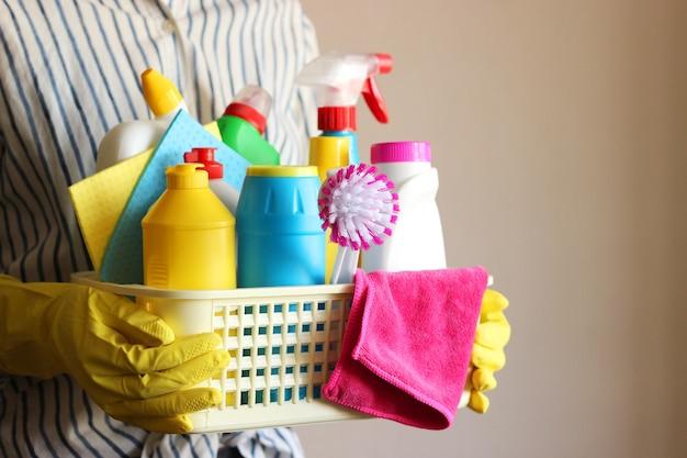 Huisvrouw houdt een mand met reinigings- en desinfectieproducten vast