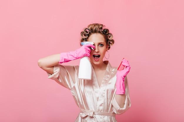 Huisvrouw in badjas en rubberen handschoenen houdt spiegel schoner