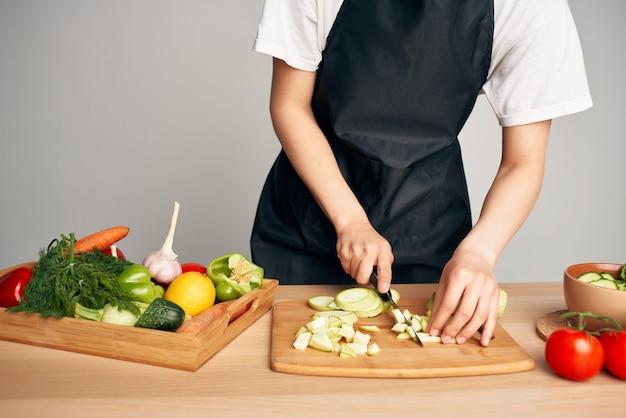 Huisvrouw in de keuken groenten snijden op een snijplank vitaminen