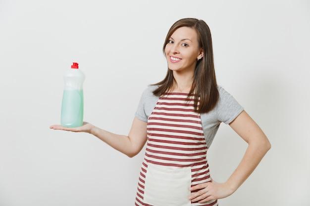 Huisvrouw in gestreepte schort geïsoleerd. mooie lachende huishoudster vrouw met fles met afwasmiddel schoner
