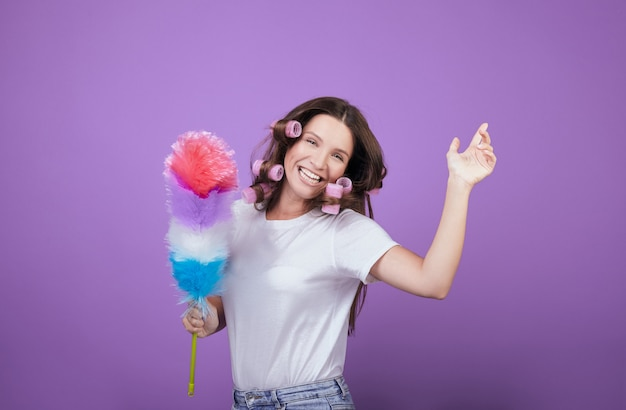 Huisvrouw in krulspelden lacht en danst tijdens het schoonmaken.