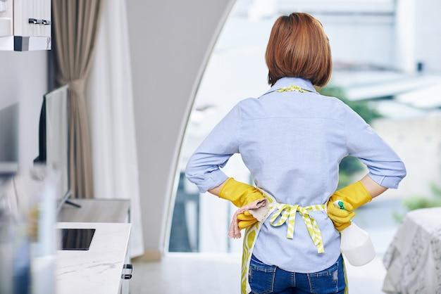 Huisvrouw in rubberen handschoenen met reinigingsspray en zachte doek kijken naar appartement na het schoonmaken, uitzicht vanaf de achterkant
