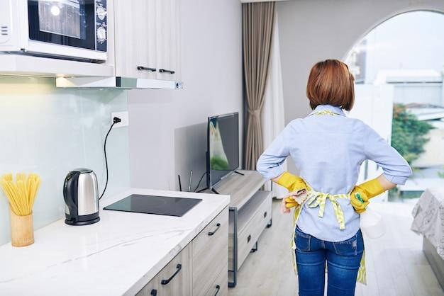Huisvrouw in schort en rubberen handschoenen kijkt naar appartement dat ze net heeft schoongemaakt, uitzicht vanaf de achterkant