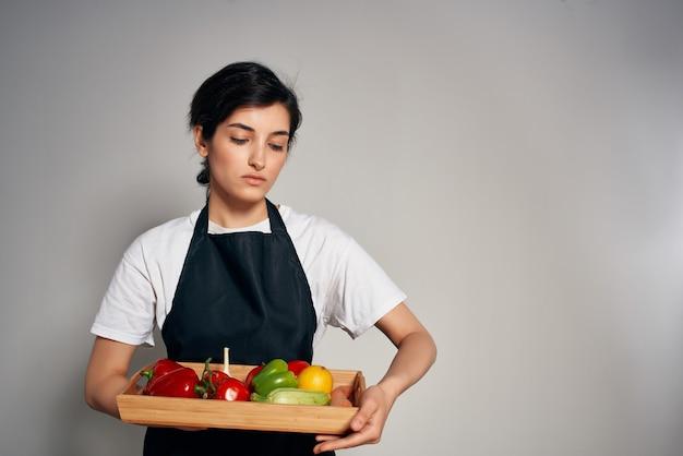 Huisvrouw in zwarte schort groenten vers voedsel lichte achtergrond