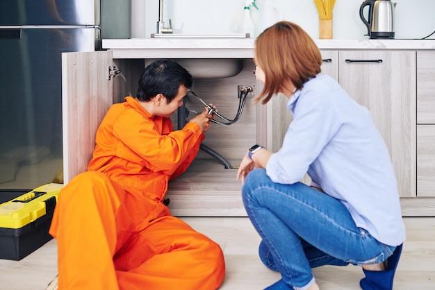 Huisvrouw kijken naar loodgieter pijp installeren onder aanrecht