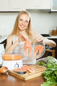 Huisvrouw koken zalm en groenten in de stoomboot