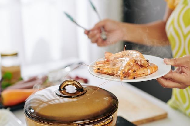 Huisvrouw kokende garnalen