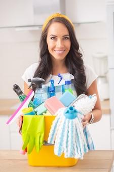 Huisvrouw lacht naar de camera die in de keuken staat, met een emmer schoonmaakspullen voor haar.