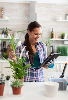 Huisvrouw leest over aarde voor bloemen tijdens het tuinieren in huis