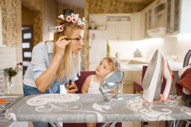 Huisvrouw make-up toe te passen op de strijkplank, kleine baby kijkt naar haar. vrouw met kind thuis samen