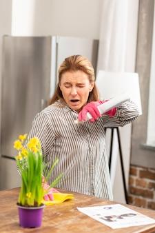 Huisvrouw met gestreept shirt die niest en allergisch is voor bloemen en chemicaliën