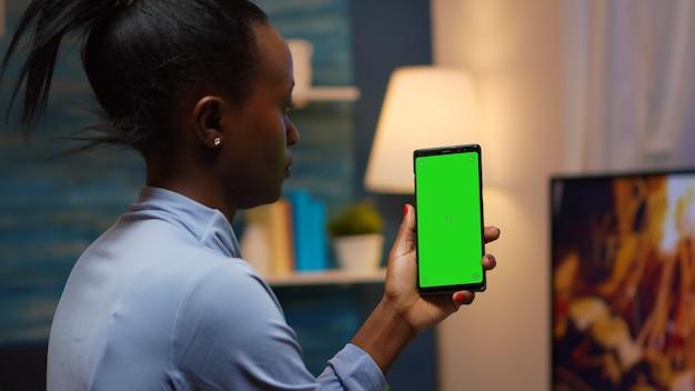 Huisvrouw met smartphone met chroma-scherm bij de hand en kijkt naar mockup. lezen op groen schermsjabloon chromakey geïsoleerde mobiele telefoonweergave met behulp van techology internet zittend op een gezellige bank