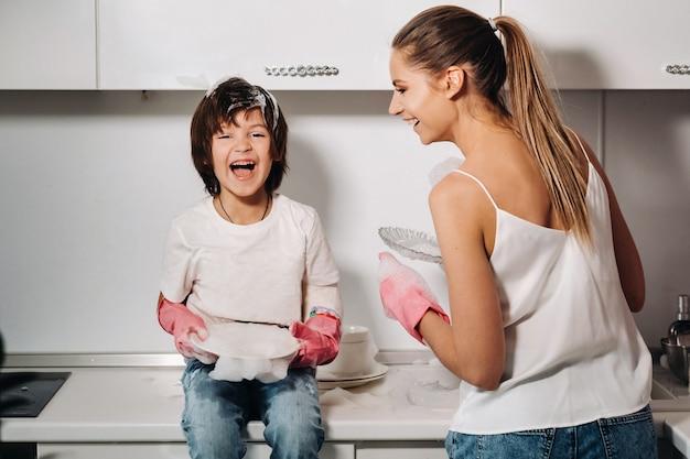 Huisvrouw moeder in roze handschoenen wast afwas met haar zoon met de hand in de gootsteen met afwasmiddel. een meisje in het wit en een kind met een cast maakt het huis schoon en wast de vaat in zelfgemaakte roze handschoenen.