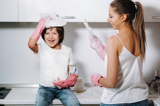 Huisvrouw moeder in roze handschoenen wast afwas met haar zoon met de hand in de gootsteen met wasmiddel. een meisje in het wit en een kind met een cast maken het huis schoon en wast de vaat in zelfgemaakte roze handschoenen.
