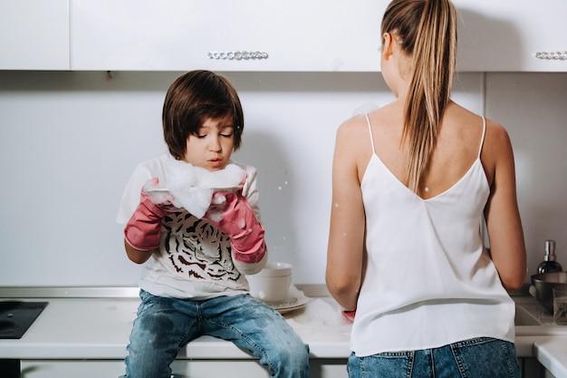 Huisvrouw moeder in roze handschoenen wast afwas met haar zoon met de hand in de gootsteen met wasmiddel.