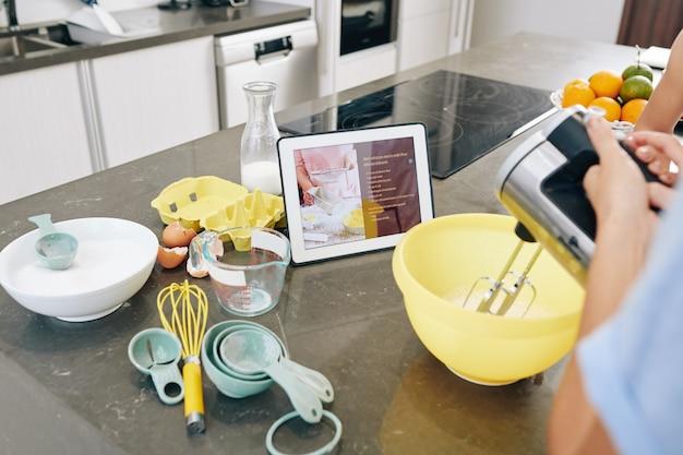 Huisvrouw na recept op tabletcomputer en het mengen van ingrediënten in een plastic kom