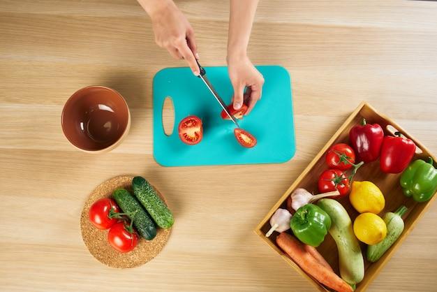 Huisvrouw op de keuken snijden groenten salade dieet