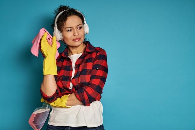 Huisvrouw poseren op camera met het reinigen van gereedschappen en benodigdheden. blauw met exemplaarruimte